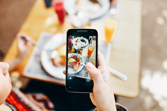 person-holding-phone-taking-picture-of-served-food